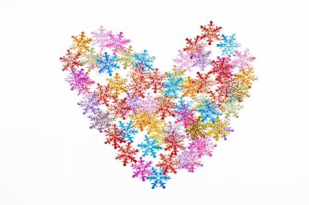 Форма сердца из красочных снежинок, изолированный белый фон. любовь к зимней концепции. искусственный рождественский снег