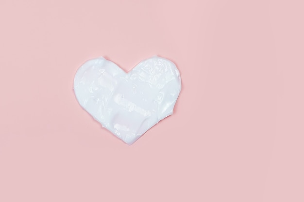 Heart shape from cream moisturiser in pink table
