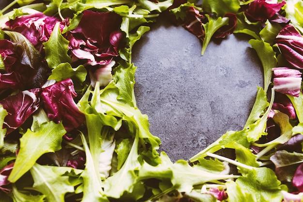 緑と紫のサラダの葉からのハートの形が背景をミックスします。コンクリートテーブル