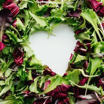 緑と紫のサラダの葉からのハートの形が背景をミックスします。白いテーブル。高品質の写真