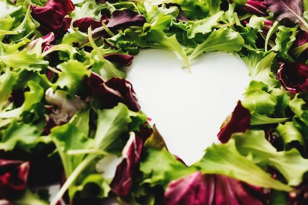 Форма сердца из зеленых и фиолетовых листьев салата смешать фон. белый стол. фото высокого качества