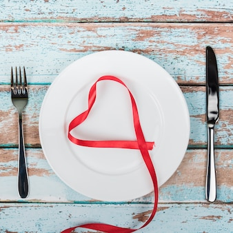 Heart shape from red ribbon on plate with cutlery