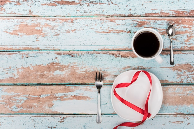 Heart shape from ribbon on plate with coffee