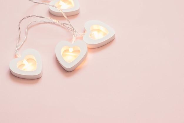 Гирлянда в форме сердца на розовом пастельном фоне. минимальное украшение на день святого валентина или свадьбу.