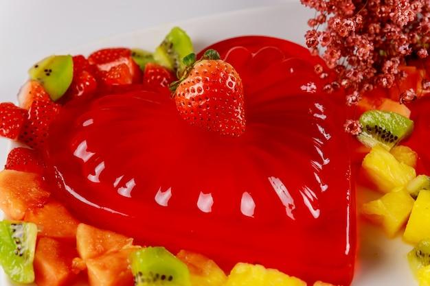 Heart shape gelatin decorated with fresh strawberry, kiwi and pineapple.