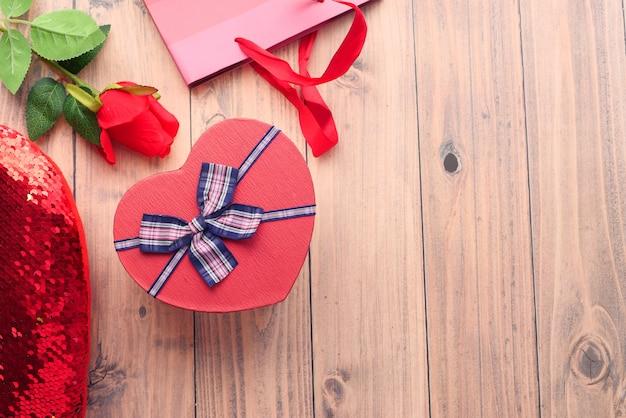 Подарочная коробка в форме сердца, сумка для покупок и цветок розы на столе