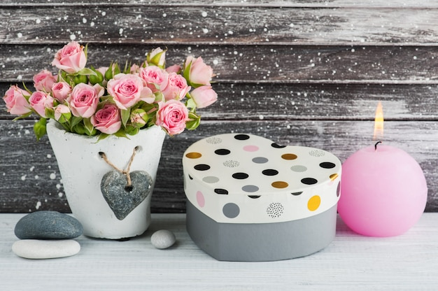 Heart shape gift, pink roses in concrete pot with candle