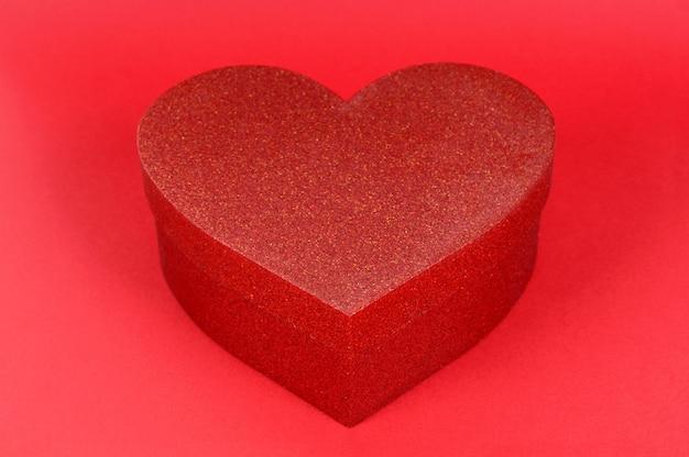 Подарочная коробка блеска формы сердца на красной бумажной предпосылке.