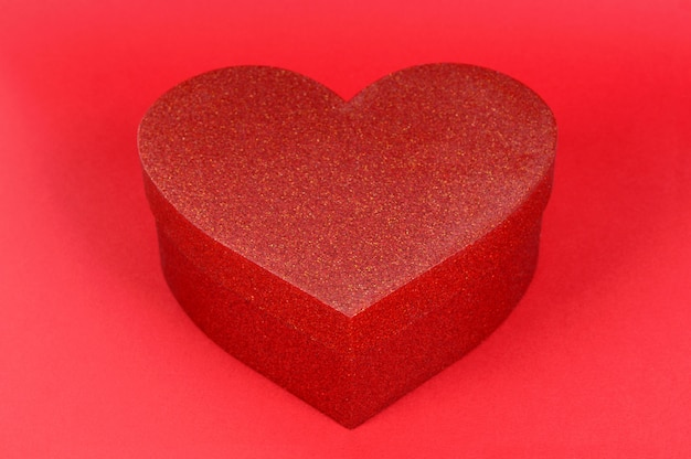 Heart shape glitter gift box on red paper background