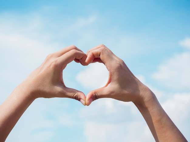 Heart shape hand on blue sky and fluffy cloud background, concept of love, relationship and romantic. female hand making finger love sign with copy space.