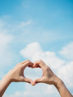Heart shape hand on blue sky and fluffy cloud background, concept of love, relationship and romantic, vertical style. female hand making finger love sign with copy space.