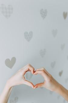 バレンタインデー、愛、優しさ、友情の概念のためのハート形の手