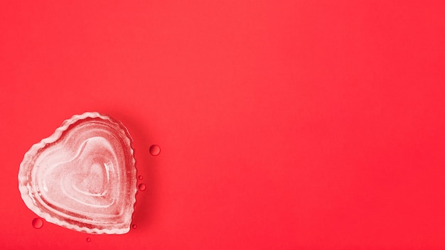 Heart shape ice cube on red background with copy space, happy valentine's day, mother's day, flat lay, top view