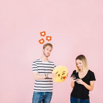 Heart shape icons over man holding kiss emoji near happy woman using mobile phone