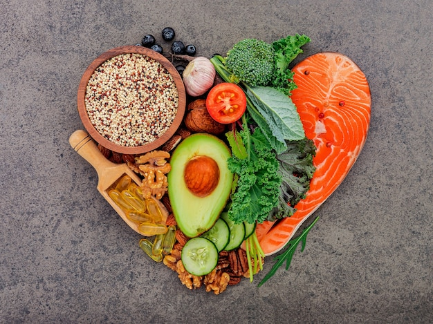 Heart shape of ketogenic low carbs diet concept. ingredients for healthy foods selection on dark stone background.