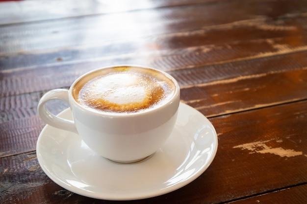 カフェレストランの木のテーブルに白いコーヒーカップでハート形ラテアート