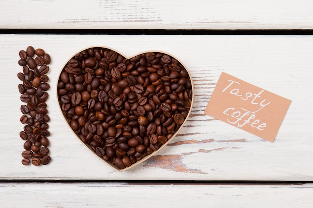 Heart shape and letter i arranged with coffee seeds. tasty coffee concept. white wooden planks.