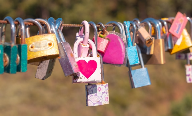 Heart shape locks, symbol of eternity love hanging on the fence of bridge by couple