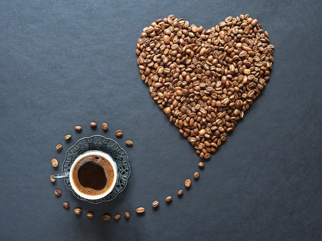 Heart shape made of coffee beans and a cup of black coffee