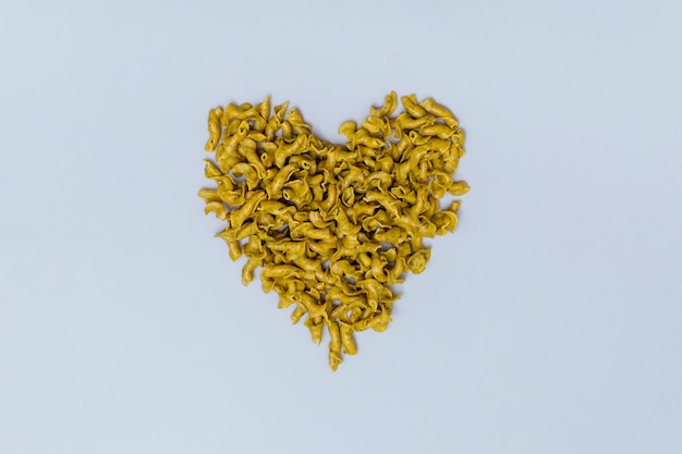 Heart shape made from italian uncooked pasta on gray background