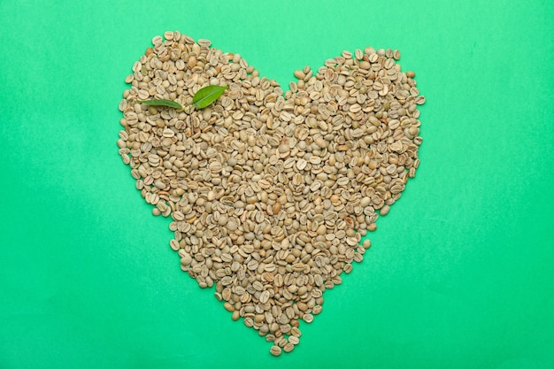 Heart shape made of green coffee beans on color