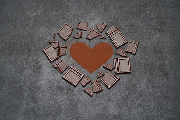 Heart shape made of grinded coffee or cocoa powder and pieces of chocolate bar on concrete background