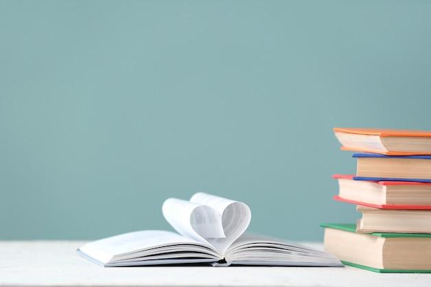 Форма сердца из книжных страниц на столе