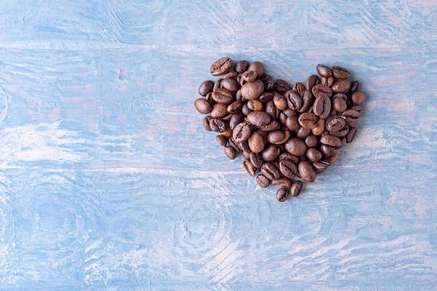 Форма сердца из кофейных зерен на синем стильном деревянном фоне