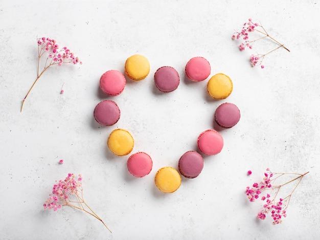カラフルなマカロンで作られたハート形。ピンクの花のフレームと白い背景
