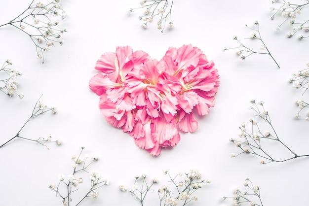 Форма сердца из цветов на белом, плоская планировка
