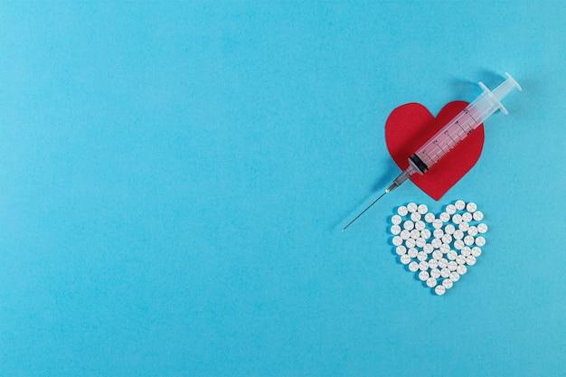 青い背景に錠剤と注射器で作られたハートの形。医薬品、健康のための容器で硬化します。医学の概念。上面図、コピースペース付きフラットレイ