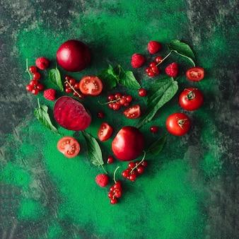녹색 잎과 향신료와 함께 빨간색 건강 식품, 과일 및 야채로 만든 심장 모양. 건강 식품 개념. 평평하다.