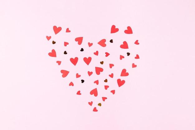 バレンタインデーのピンクの背景のグリーティングカードに赤いハートとスパンコールで作られたハートの形