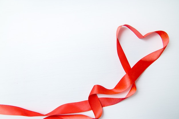 Heart shape made of red ribbon on white wooden background