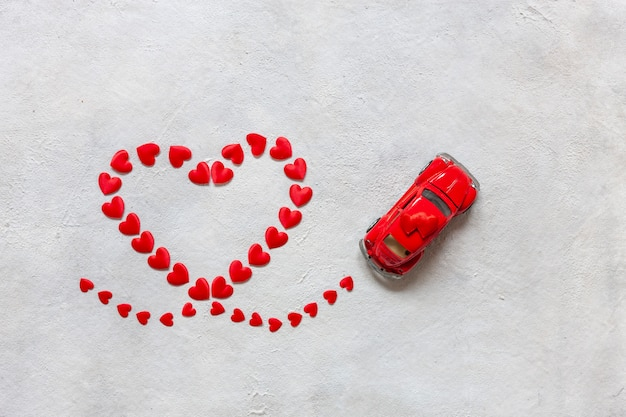 Heart shape made of small red hearts and a red toy car