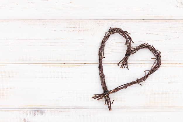 Heart shape made of twigs - wooden symbol of love on a white background.