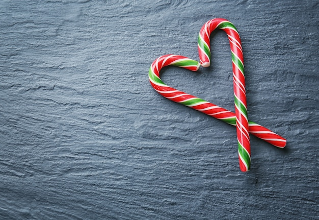 Heart shape made with christmas candy canes on gray