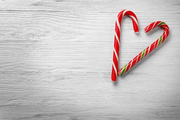 木製の背景にクリスマスキャンディケインで作られたハートの形
