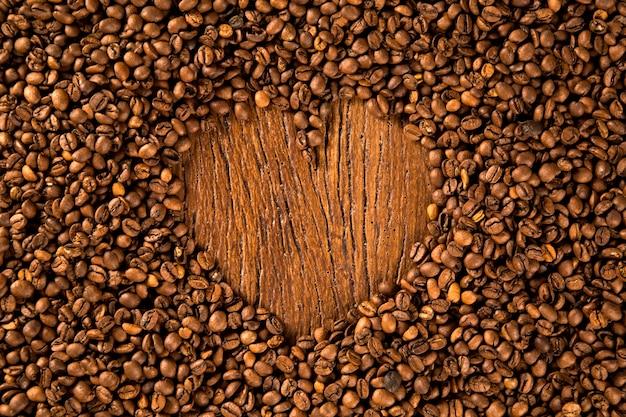 나무 테이블에 커피 콩으로 만든 하트 모양