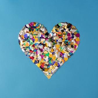 Форма сердца сделана из красочного конфетти из металлической фольги.