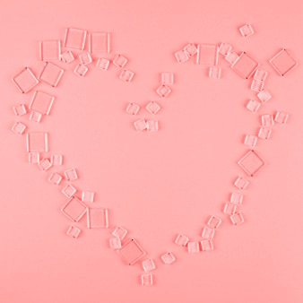Heart shape made with different type of transparent cubes on coral background