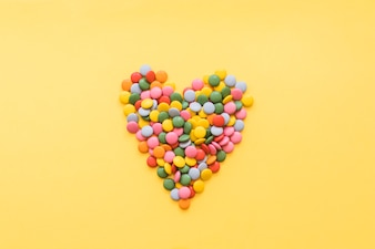 Heart shape made with gems candies on yellow backdrop