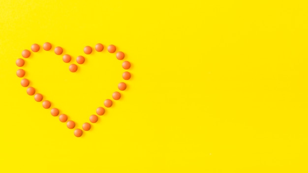 Heart shape made with pills on yellow background