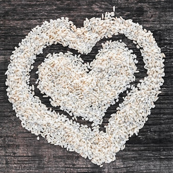 Heart shape made with uncooked white rice on wooden backdrop