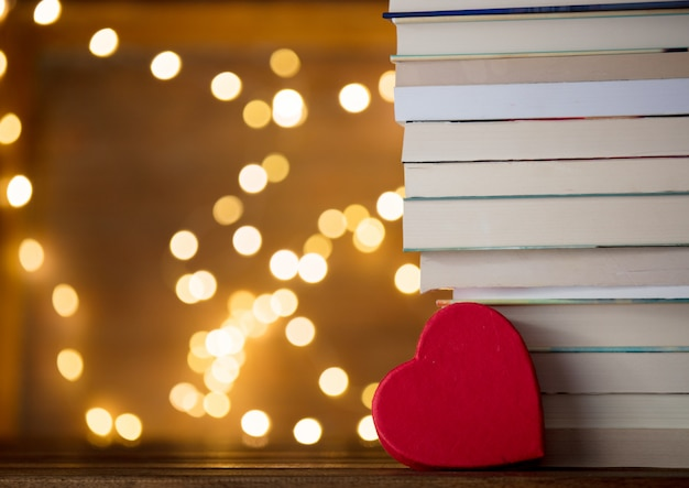 Heart shape near pile of books and fairy lights