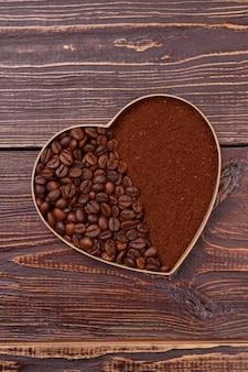 Форма сердца из кофейных зерен и растворимого кофе. коричневая деревянная поверхность.
