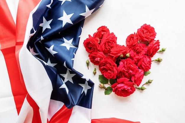 Форма сердца из красных роз с плоской планировкой сверху на флаге сша