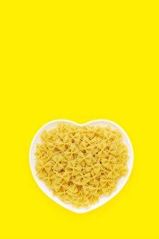 黄色の垂直背景、コピースペースに未調理のパスタ蝶ネクタイとハート型プレート。バタフライマカロニ、デュラム全粒粉から作られたイタリア料理の材料、ヘルシーフードディナーレシピ。