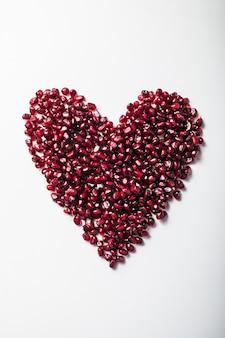 Семена граната в форме сердца на белом.
