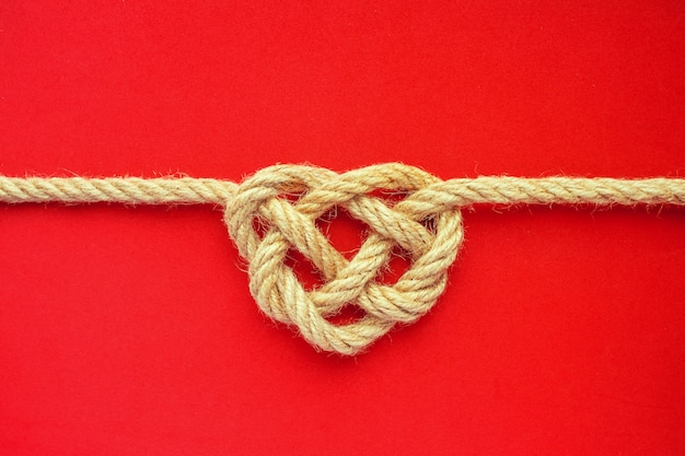 Heart shape rope knot on red background. jute rope celtic knot.  love concept.